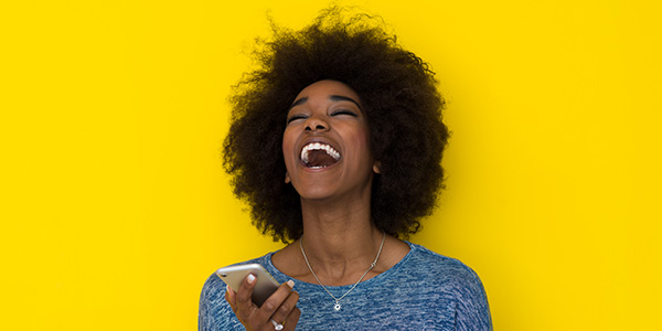 Positive laughing woman on sunny yellow background