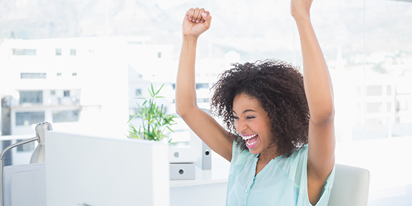Happy african-american woman at desk celebrating