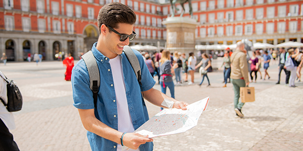 Happy man on vacation looking at map in city square