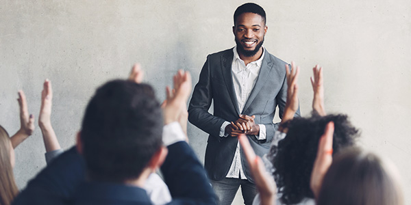 Smiling african-american man answering raised hands in meeting